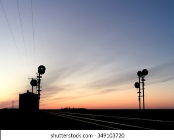 Pair of Railway Signals Silhouetted against Sunset Sky