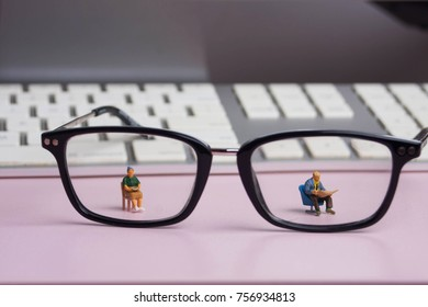Pair of reading glasses on a desk. Miniature people magnified by a pair of eye glasses. Optical aid for middle aged or elderly folks. Depicted in miniature.