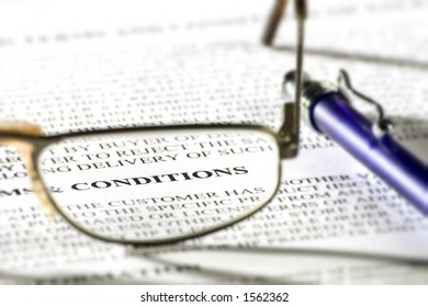 Pair of reading glasses on paper with word 'conditions' in focus