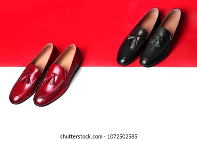 Pair of red and black stylish loafers. Red and white paper background