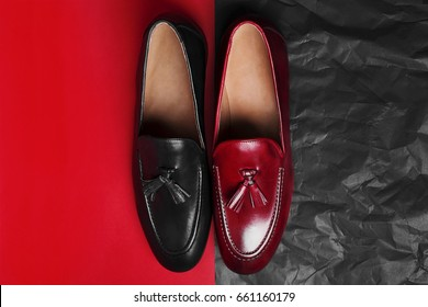 Pair of red and black stylish loafers. Red and black paper background.