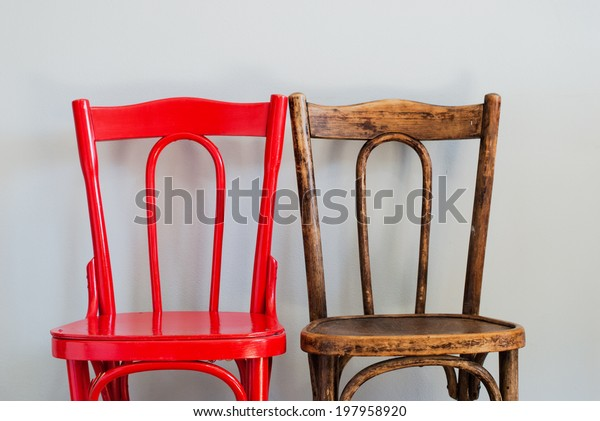 Pair of Red and Brown Chairs on a Grey Wall