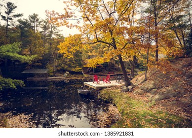 A pair of red chairs on a cottage dock
