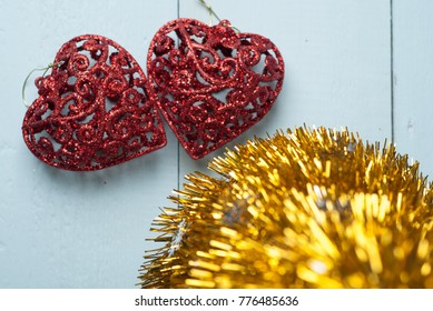 Pair of red decorative hearts on wooden background, Christmas tinsel, a banner on 14 Feb, template for Valentine's day