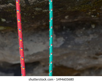 Pair of red and green climb ropes in detail. Used light nylon  rope on natural background