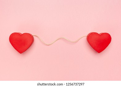 Pair of red hearts connected with a string of twine on pink background.