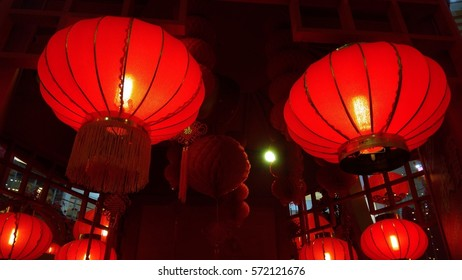 A Pair of Red Lantern Hang on Ceiling with few at the background