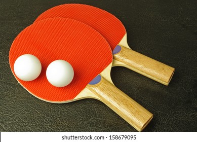 Pair of red ping-pong rackets and two white balls on black background