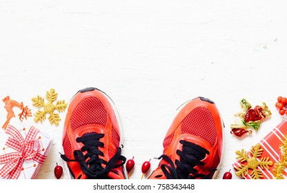 Pair of red sport shoes with Christmas decoration items and presents boxes laid on grunge white wooden floor background, top view with copy space