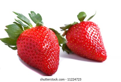 A pair of red strawberries over a white background.