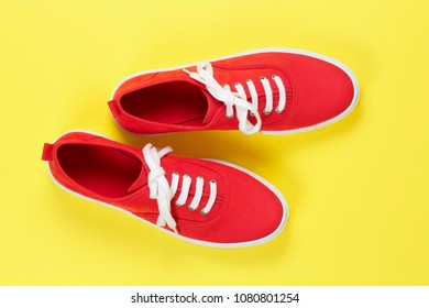 pair of red suede shoes on yellow surface
