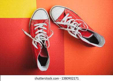 Pair of red used sneakers on colorful background, view from top. Clothes mockup