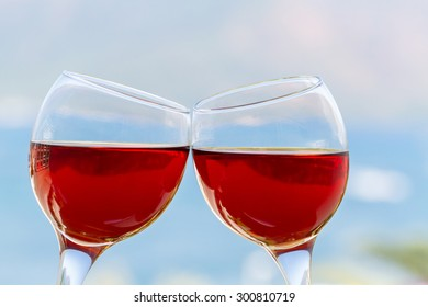 Pair of red wine glasses on landscape background