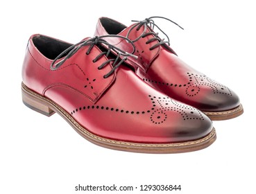 A pair of red wing tip dress shoes on an isolated background