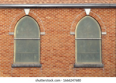 a pair of retro arched vintage church windows on a red brick wall