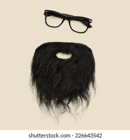 a pair of retro eyeglasses and a beard forming a man face on a beige background