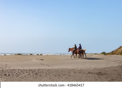Pair of riders on horseback on ocean beach in California