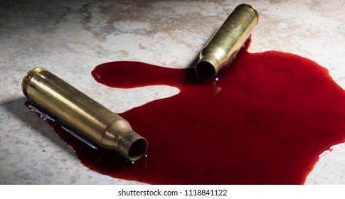 Pair of rifle cartridges that have been shot on the floor with blood