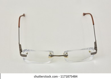 Pair of rimless eye-glasses on white background.