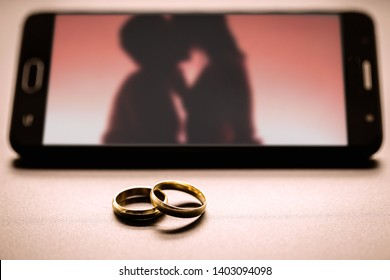 Pair of rings next to a smartphone, with an image of a blurred couple kissing on the screen. Concept of lovers or marital betrayal, infidelity.
