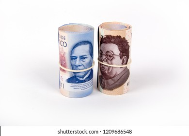 a pair of rolls of Mexican bills side by side, tied with garters, on a white background