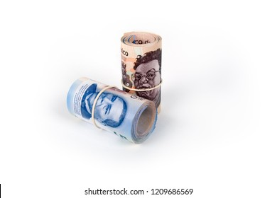 a pair of rolls of Mexican bills, tied with garters, on a white background