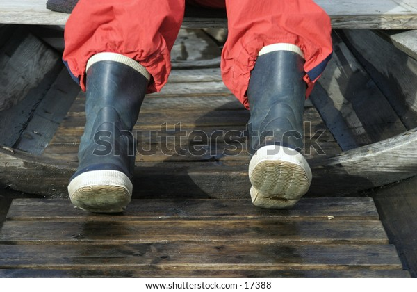 A pair of rubber boots in an old wooden boat.
