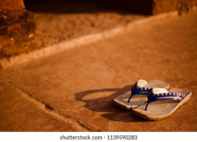 A pair of rubber made shoes kept on a concrete surface isolated unique photo