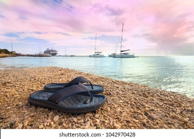 a pair of rubber sandals on the sand at a beach of Bonaire with the sea and boats in the background.