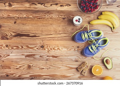 Pair of running shoes and healthy food composition on a wooden table background
