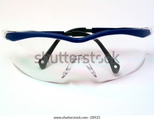 A pair of safety goggles against off white background.