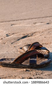A pair of sandals or flip flops left by its traveler owner on the beach sand while take a dip on the peaceful waters of lonely beach, this is the kinf of life that averyone pursuit all the time