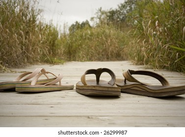 A pair of sandals on a boardwalk at the beach