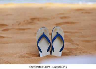 Pair of sandals on sandy beach closeup blur ocean waves background