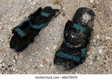 A pair of sandals on the white sand beach