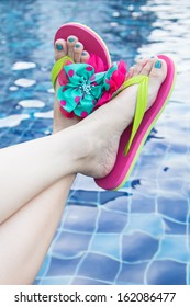 Pair of sandals sitting on the edge of a pool.