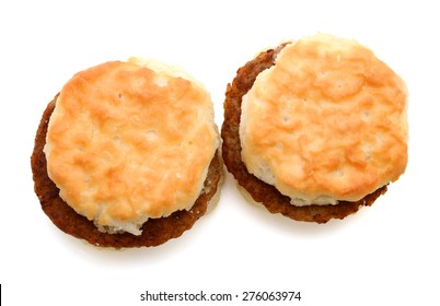 a pair of sausage patty with baked biscuit on white background