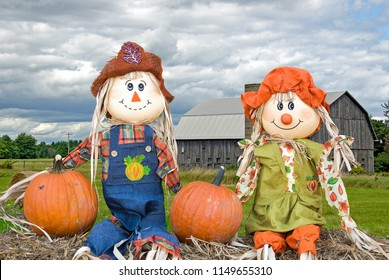 pair of scarecrow dolls on hay bale with rural wooden barn in background