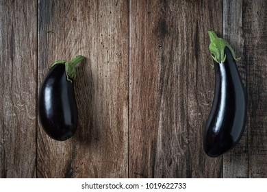 Pair of Shiny Eggplants on rustic wooden bacground. Copy space.