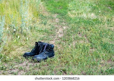 a pair of shoes left by a man on the road in a field, abandoned shoes