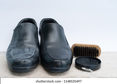 a pair of shoes made by leather with shoe brush and black wax on wooden board white background.Before and after shoeshine.