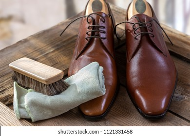 Pair of shoes with shoe maintenance set on wooden table