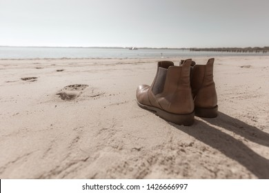 a pair of shoes standing on the beach