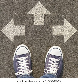Pair of shoes standing on a road with three white arrow