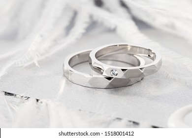 Pair of silver wedding rings with diamond on gray background with feathers. Geometric shape wedding rings band with gemstone in women ring