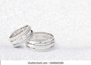 Pair of silver wedding rings with diamonds on white glossy background with bokeh. White gold wedding ring bands with gemstones on female ring