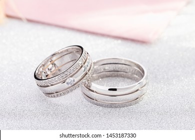 Pair of silver wedding rings with diamonds on white glossy background.White gold wedding ring bands with gemstones on female ring
