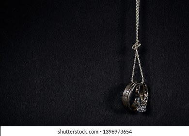 pair of silver wedding rings hanging from a chain with knot isolated on black background