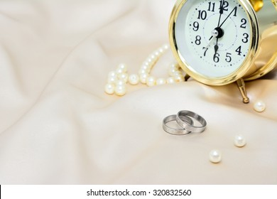 Pair of silver wedding rings with yellow pearl and gold clock on silk background for wedding or valentines days concept time to marry