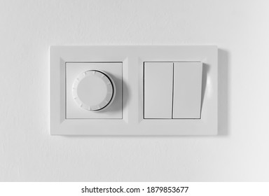 Pair of simple light switches with dimmer. Inexpensive plastic mechanical double switch with thermostat against white wall. Old air conditioner control panel. Smart Home Climate Control Appliances